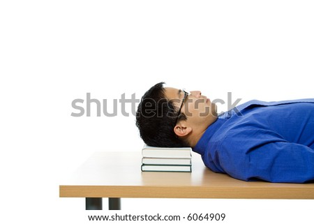 An isolated shot of a businessman sleeping on a table using books as the pillow - stock photo