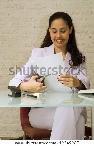 An isolated shot of a businesswoman cutting papers. - stock photo