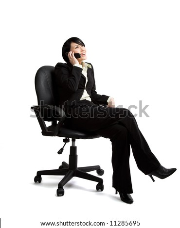 An isolated shot of a businesswoman sitting on a chair and talking on the phone - stock photo