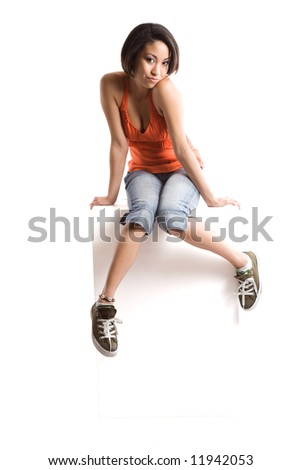 An isolated shot of a casual woman sitting on top of a blank billboard, plenty of copyspace