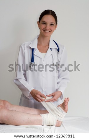 An isolated shot of a doctor/nurse bandaging a women's sprained ankle. - stock photo
