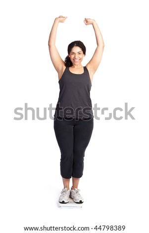 An isolated shot of a happy woman standing on a weight scale