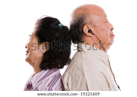 An isolated shot of a senior asian couple listening to music - stock photo