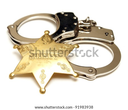 An isolated shot of a sheriff badge and pair of handcuffs. - stock photo