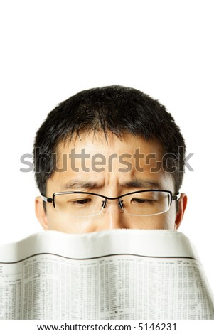 An isolated shot of a stressed businessman reading a financial newspaper - stock photo
