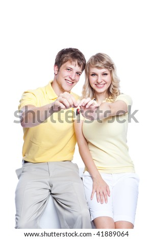 An isolated shot of a young caucasian couple holding a set of keys - stock photo
