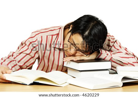 An isolated shot of a young man falling asleep while reading books - stock photo