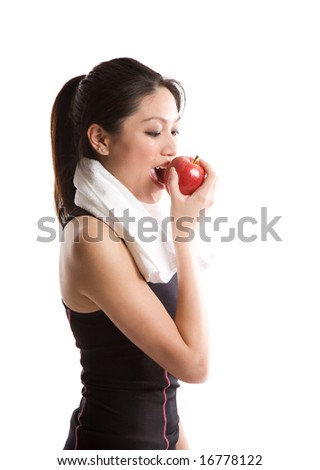 An isolated shot of an asian girl eating an apple after exercise