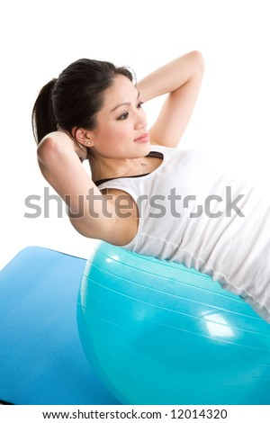 An isolated shot of an asian woman doing sit-up on an exercise ball - stock photo