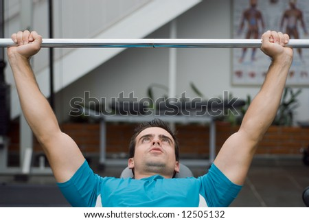 An isolated shot of male weightlifter bench pressing a barbell. - stock photo