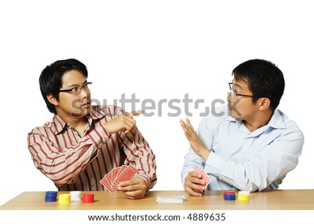 An isolated shot of two men playing poker with one of them get caught for cheating - stock photo
