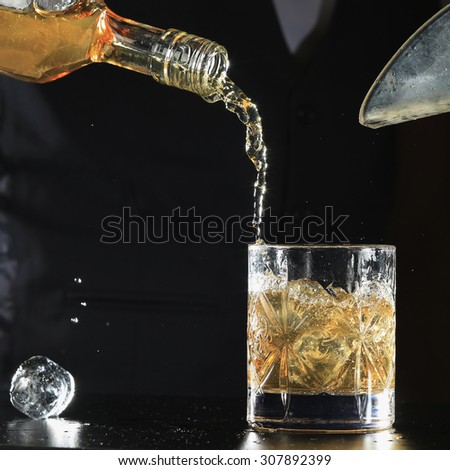 An isolated shot of whiskey with a splash on a black background