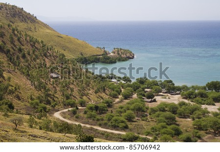 An isolated village on a hillside next to a pristine beach in timor leste