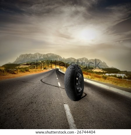 an isolated wheel running on a country road - stock photo