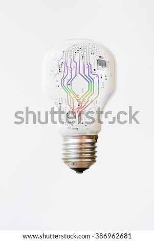 An isolated white light bulb with rainbow colored, electronic lines surging through the middle. Vertical  - stock photo