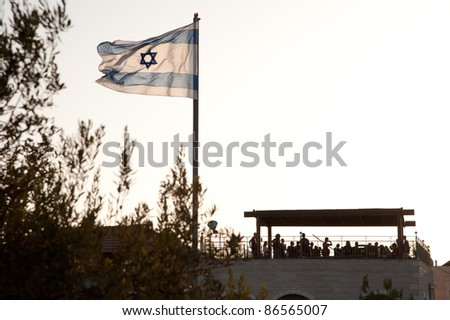 An Israeli flag flies over the Jewish settlement of Beit Hoshen on the Mount of Olives in East Jerusalem. - stock photo