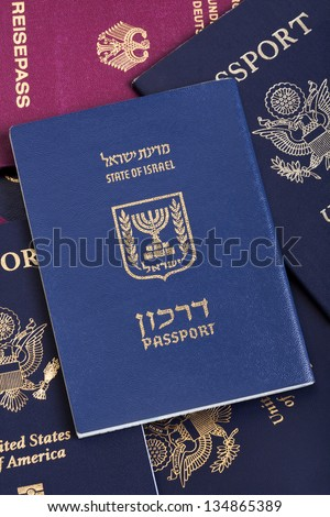 An Israeli passport resting on a stack of American and German passports. - stock photo