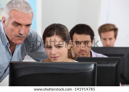 An IT teacher giving a class. - stock photo