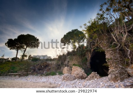 An italian beach with an ancient roman ruin which became a cave covered by trees and roots - stock photo