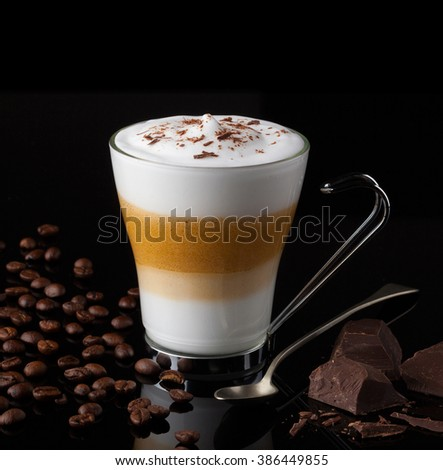 An Italian cappuccino coffee with creamy milk and chocolate on a shiny black surface. - stock photo