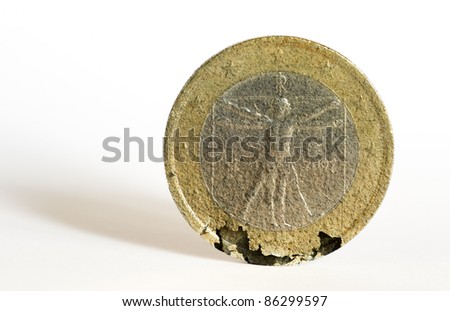An Italian one euro coin crumbles under the strain of the economic crisis. - stock photo