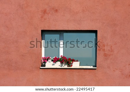 An Italian window is decorated with flowers in the summer.