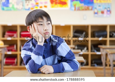 An Japanese elementary boys bored in the classroom desk