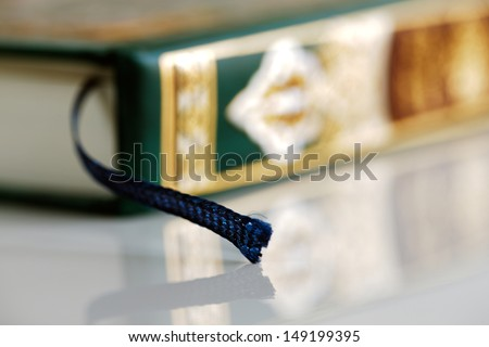 An macro image of the bookmark in the Quran. The Quran literally meaning 'the recitation' is the central religious text of Islam, which Muslims believe to be the verbatim word of God or Allah - stock photo
