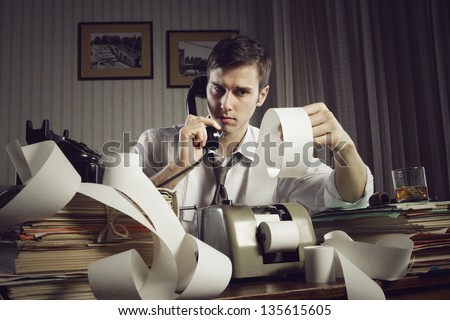 An male accountant at telephone  preparing income taxes - stock photo