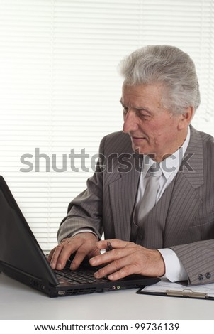 an mature man sitting at the computer on a light background