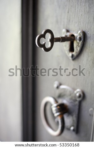 an metal key inserted into an old door pictured with a narrow depth of field