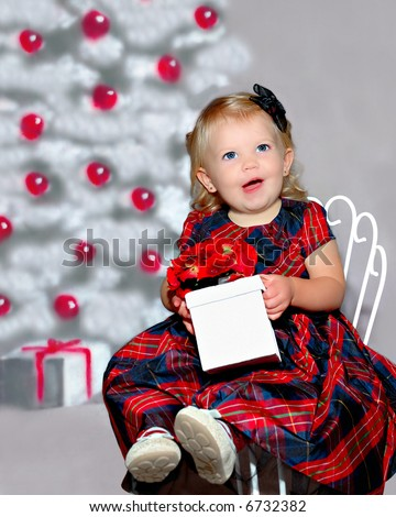 An 18 month old toddler girl child sitting in a chair in her holiday dress in front of a christmas tree, holding a gift with an excited expression on her face.