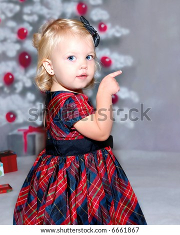 An 18 month old toddler girl child standing in front of the christmas