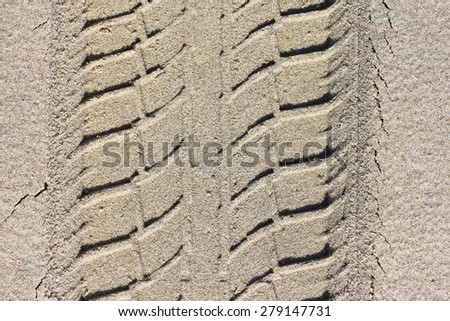 An oblique tire pattern in yellow sand