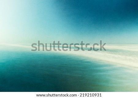 An ocean seascape with blurred panning motion.  Image displays abstract, split-toned colors and a pleasing paper grain and texture.
