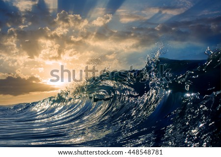 An ocean sunset shorebreak in side view with bokeh flares. Big beautiful high contrast sunrise wave swirling. Bright sun shining on blue sky with colorful clouds. - stock photo