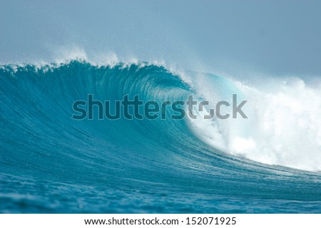 An ocean wave breaks over a shallow reef in the Maldives. - stock photo