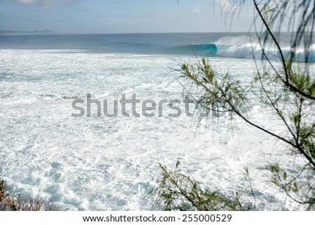 An ocean wave breaks over a shallow sandbank in Mozambique. - stock photo