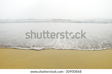 An ocean wave coming from the fog and reaching the sand on the Pacific coast in California. - stock photo