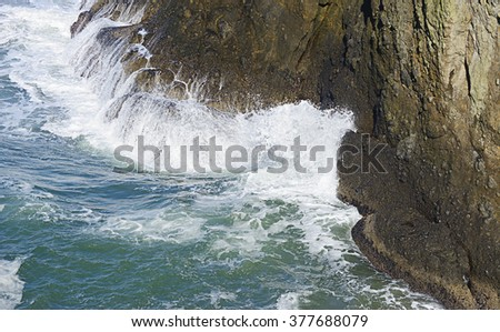An ocean wave meets the base of a sea cliff at Yaquina Head Outstanding Natural Area, Newport, Oregon. The water of the wave cascades down from the rock.  - stock photo