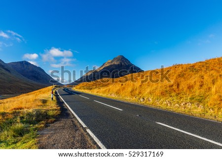 An October early morning warm light over a road in Highlands leading to Glencoe, Scotland, UK