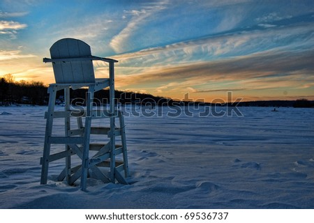 An off-season lifeguard chair stands in deep snow on the shore of a lake. Ice fishermen in the distance.