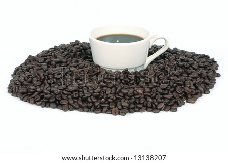 An off white mug filled with coffee and surrounded by beans. - stock photo