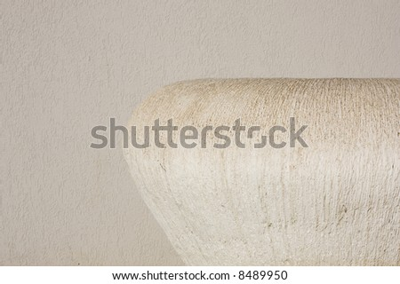 An off-white textured cement urn in front of a cement wall. - stock photo