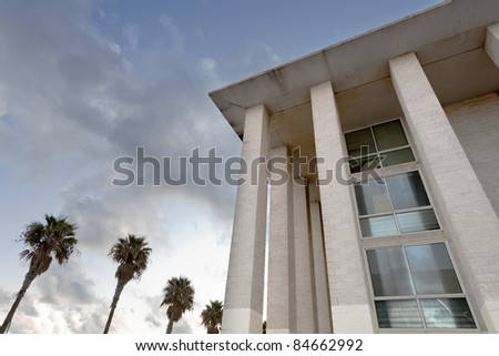 an office building surrounded by palm trees