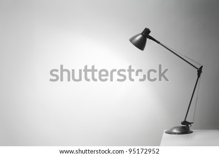 An office desk lamp illuminating the background. Lots of copy space. - stock photo