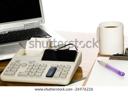 An office desk with a cup of coffee, a calculator and a laptop, isolated against a white background - stock photo