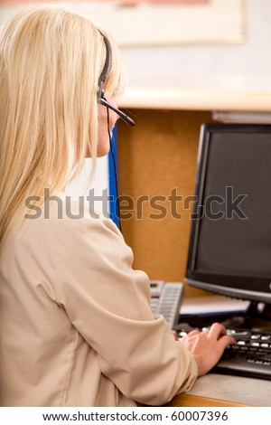 An office receptionist working at a computer and taking calls - stock photo