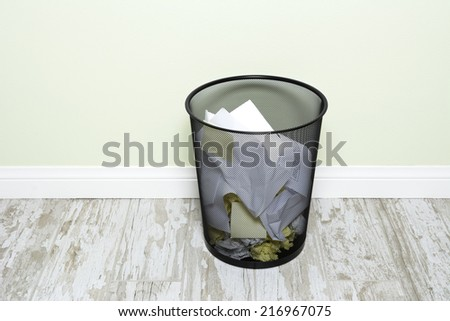 An office trashcan filled with wads of crumpled paper, sticky notes and folded paper.  - stock photo