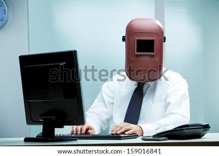 An office worker at his desk wearing a welder's mask - stock photo
